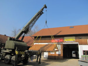 Das komplette Dach der Kapelle wird mit Hilfe eines Krans verladen